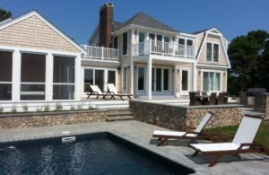 backside of large custom built home with a pool