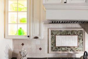 Tile backsplash and a lit up glass cabinet