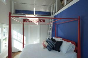 Children's beddrom with red framed metal bed