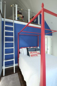 Children's beddrom with red framed metal bed and a ladder up to a loft